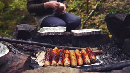 temperada : 4k, slow motion. the tourist is cooking sausages on a mini grill in the forest. close-up