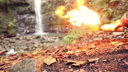 tocha : 4k, slow motion. the tourist turns on the gas burner at the foot of the mountain, against the waterfall. Vídeos