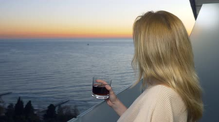 suite : a woman is standing on the balcony of the resort with a view of the sea. drinks a cocktail in the evening looking at the sunset. 4k Stock Footage