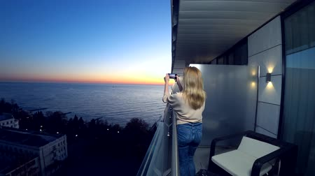 kék háttér : An attractive young woman using a smartphone at the balcony of a spa hotel, A woman is photographing a sunset by the sea using an application on a smart cell phone. 4k