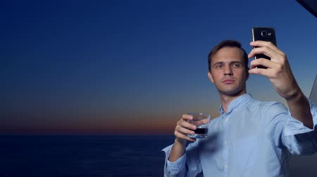 water display : An attractive young man using a smartphone on the balcony of a spa hotel, a man takes pictures of the sunset by the sea, using an application on a smartphone. 4k close-up