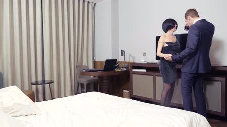 стриппер : couple, male businessman and brunette woman with short hair drink alcohol on bed in hotel room. 4k
