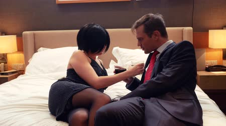 striptease : couple, male businessman and brunette woman with short hair drink alcohol on bed in hotel room. 4k