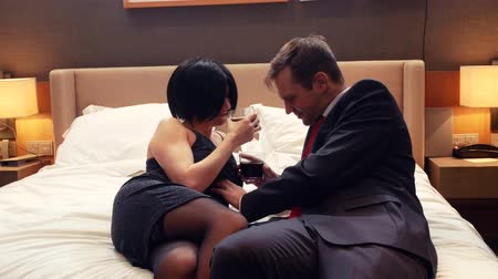 trafficking : couple, male businessman and brunette woman with short hair drink alcohol on bed in hotel room. 4k