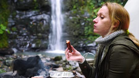temperada : 4k, slow motion. tourist girl eating a sausage grill in the forest near a tent against a waterfall background.