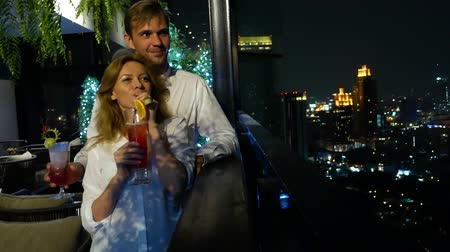 hayran olmak : Happy couple hugging, kissing and drinking cocktails on the terrace of the bar overlooking the skyscrapers, at night, 4k, blur background. romantic date, honeymoon. Stok Video
