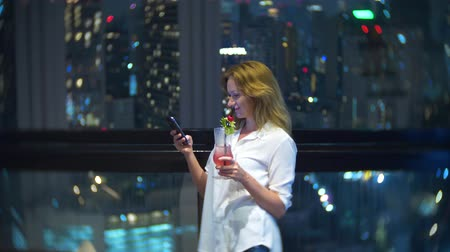 skybar : Young, beautiful blond woman using a smartphone and drinking a cocktail, on a bar terrace overlooking the skyscrapers at night. 4k, background blur. Stock Footage