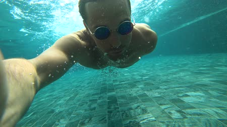 calções de banho : A young white handsome male doing an underwater selfie on an action camera. Portrait of a young man with glasses taking himself off to the camera under water. 4k Vídeos