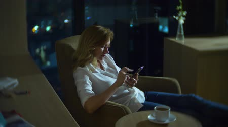 запятнанный : Young, beautiful blond woman using a smartphone, on a chair in a room with a panoramic window overlooking the skyscrapers at night. 4k, blur the background.