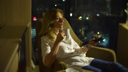 stained glass : Young, beautiful blond woman using a smartphone, on a chair in a room with a panoramic window overlooking the skyscrapers at night. 4k, blur the background.