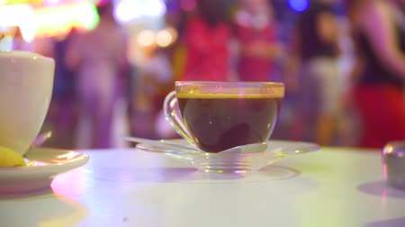 porcelana : a cup hot coffee on a table in a cafe, on a terrace overlooking a busy pedestrian street. evening, backlight, 4k, background blur