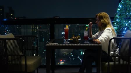 skybar : Young woman blonde relaxing and drinking cocktail in bar with a view of the skyscrapers at night. 4k, background blur