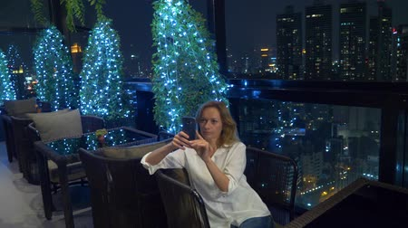 skybar : Young, beautiful blond woman using a smartphone, on a bar terrace overlooking the skyscrapers at night. 4k, background blur. Stock Footage