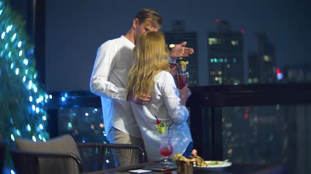 skybar : Happy couple hugging, kissing and drinking cocktails on the terrace of the bar overlooking the skyscrapers, at night, 4k, blur background. romantic date, honeymoon. Stock Footage