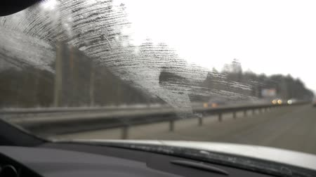 wiper : the car rides along the winter road, a view from inside through a poorly cleaned frozen glass. 4k