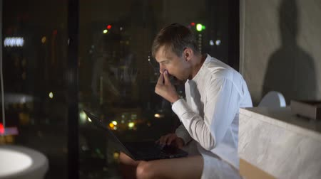уборная : A man is sitting in the toilet in a luxurious restroom with a panoramic window at night with a laptop and works. 4k