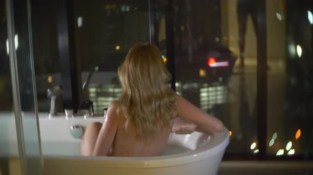 hot tub : Beautiful woman enjoying a relaxing bath in a luxurious bathroom with a window at night. The concept of a way of life and beauty. view from the window to the skyscrapers. 4k