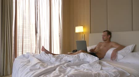 bezsennosć : Young man sitting in bed with his laptop computer open and smartphone. Hes working on it. 4k
