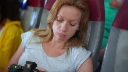 sono : 4k, close-up, a woman in an airplane browsing photos from the camera.