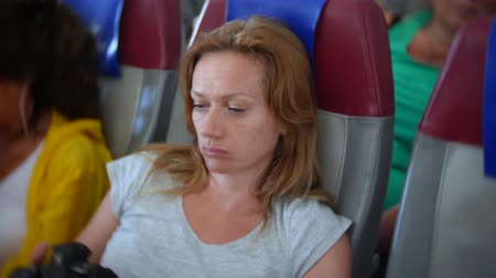 waking : 4k, close-up, a woman in an airplane browsing photos from the camera.