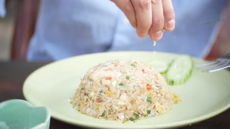seafood dishes : close-up. 4k. man squeezes lime juice on a dish with stir fried Jasmine rice with egg and shrimps, decorated with cucumber.