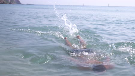 урод : 4k, slow-motion shooting, a young man dives into the sea in sunglasses. emerges