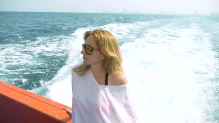 посетитель : A beautiful woman is standing on the stern of the ship. Waves in the background, slow motion, 4k