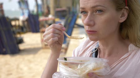 seafood dishes : woman eating Thai soup Tom Yam sitting on the beach, 4k slow-motion