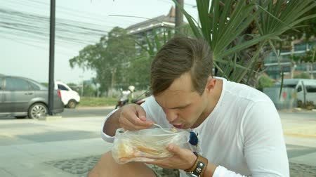 tom : man eating Thai soup Tom Yam sitting on the beach, 4k slow-motion Stock Footage