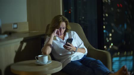использование : Young, beautiful blond woman using a smartphone, on a chair in a room with a panoramic window overlooking the skyscrapers at night. 4k, blur the background.