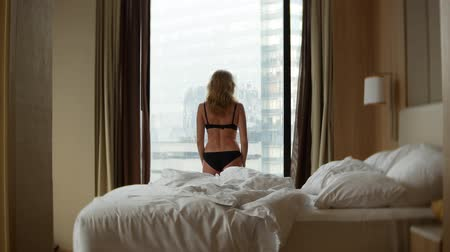 cover : A blond woman in lingerie, opens the curtains on the window, view from the window to the skyscrapers. slow motion. 4k
