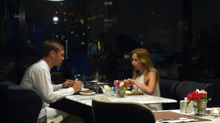 cheers : Happy couple talking and having dinner in a bar overlooking skyscrapers, in the evening, 4k, blur background