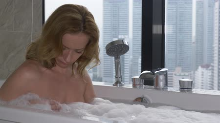 hot tub : Beautiful Woman enjoying relaxing bath in luxury bathroom with a window. Lifestyle and beauty care concept. view from the window to the skyscrapers. 4k