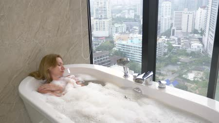 купаться : Beautiful Woman enjoying relaxing bath in luxury bathroom with a window. Lifestyle and beauty care concept. view from the window to the skyscrapers. 4k