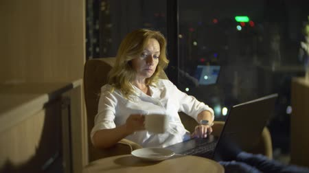 stained glass : Young, beautiful blond woman using a laptop, on a chair in a room with a panoramic window overlooking the skyscrapers at night. 4k, blur the background