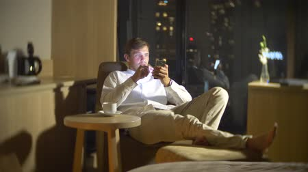 запятнанный : Young, beautiful man using a smartphone, on a chair in a room with a panoramic window overlooking the skyscrapers at night. 4k, blur the background.