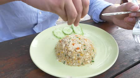 yasemin : close-up. 4k. man squeezes lime juice on a dish with stir fried Jasmine rice with egg and shrimps, decorated with cucumber.