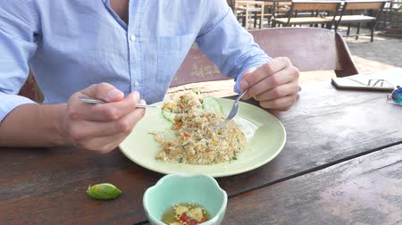 garfos : close-up. 4k. man squeezes lime juice on a dish with stir fried Jasmine rice with egg and shrimps, decorated with cucumber.