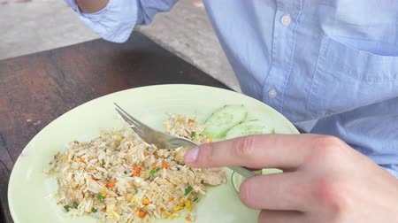 evaporate : close-up. 4k. man squeezes lime juice on a dish with stir fried Jasmine rice with egg and shrimps, decorated with cucumber.