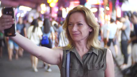 на камеру : Portrait of elegant young woman making selfie on crowded street at night, 4k, slow-motion, blur background