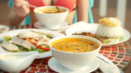calcário : prawn spicy soup is a Thai dish with sour and spicy taste. busty girl in a bikini eats Tom Yam at a table by the pool. 4k, slow-motion, close-up. concept of travel tourism