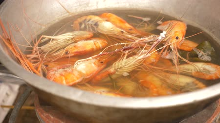 wok food : 4k, close-up, someone cooks shrimps in a saucepan. Slow motion
