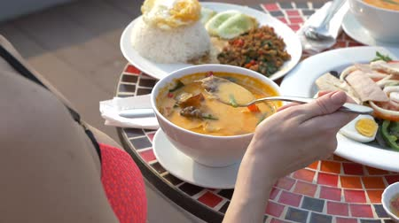 vápenné mléko : prawn spicy soup is a Thai dish with sour and spicy taste. busty girl in a bikini eats Tom Yam at a table by the pool. 4k, slow-motion, close-up. concept of travel tourism