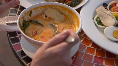 calcário : prawn spicy soup is a Thai dish with sour and spicy taste. some are scooping prawn spicy soup. 4k, slow-motion, close-up