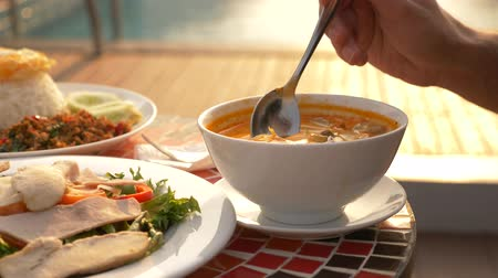 calcário : Shrimp soup is a Thai dish with a sour and spicy taste. the man is eating Tom Yam at a table by the pool. 4k, slow motion, close-up. concept of tourism tourism Stock Footage