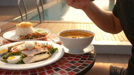vápenné mléko : Shrimp soup is a Thai dish with a sour and spicy taste. the man is eating Tom Yam at a table by the pool. 4k, slow motion, close-up. concept of tourism tourism Dostupné videozáznamy