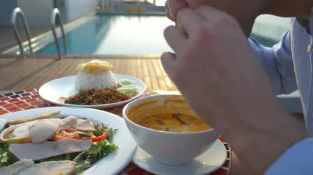 çili : Shrimp soup is a Thai dish with a sour and spicy taste. the man is eating Tom Yam at a table by the pool. 4k, slow motion, close-up. concept of tourism tourism Stok Video