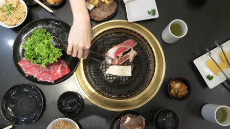 tongs : Korean barbecue grill. people cook and eat dishes cooked on a Korean grill in a restaurant. 4k, close-up.