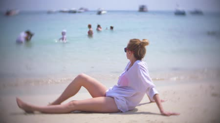 muse : A thoughtful, sad woman, sits alone on the sand in a crowded beach, 4k, slow-motion. background blur Stock Footage