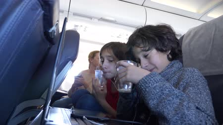 korku : 4k, close-up, children, passengers drink water from disposable cups in the plane during the flight against the porthole. Stok Video